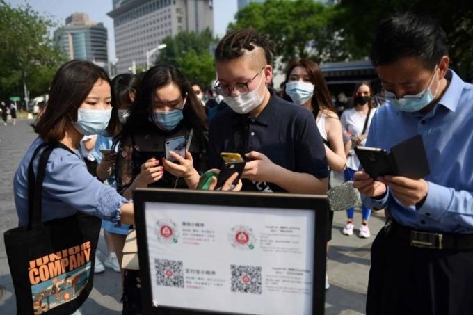 Người dân Trung Quốc dùng mã QR để chứng minh tình trạng sức khỏe và lịch sử di chuyển trước khi vào trung tâm mua sắm ở Bắc Kinh vào tháng 5. Ảnh: AFP.