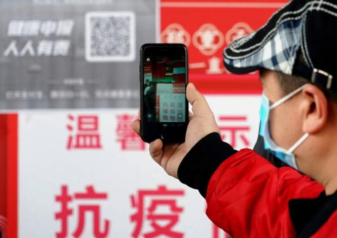 Người dân Trịnh Châu quét mã QR trước lối vào siêu thị vào tháng 2. Ảnh: Xinhua.