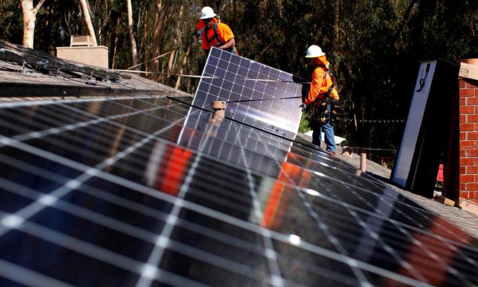 Lắp đặt pin Mặt Trời tại một căn hộ ở bang California. Ảnh: Reuters.