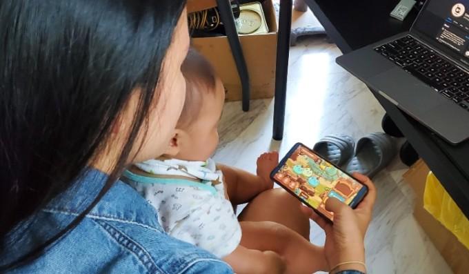 Một phụ nữ Malaysia đang chơi game Axie Infinity khi đang trông con nhỏ. Ảnh: Lorcan Gaming.
