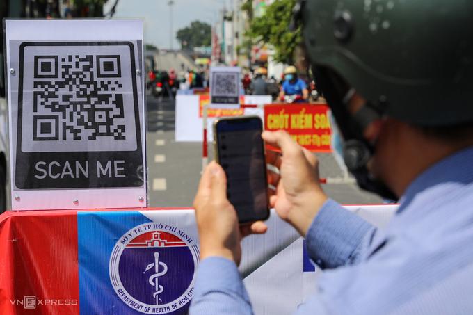 Người dân quét mã QR Code khai báo y tế điện tử tại một chốt kiểm dịch Covid-19. Ảnh:Quỳnh Trần